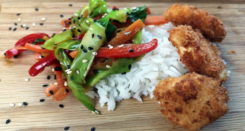 Wokade grönsaker med friterad tofu serverad på kokt ris.