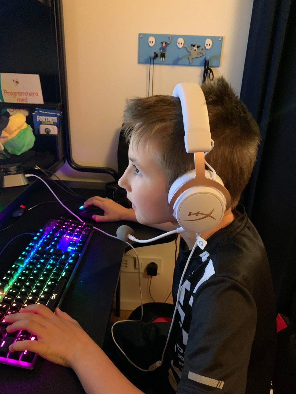 Pojke spelar PC med HyperX Cloud Mix Rose Gold