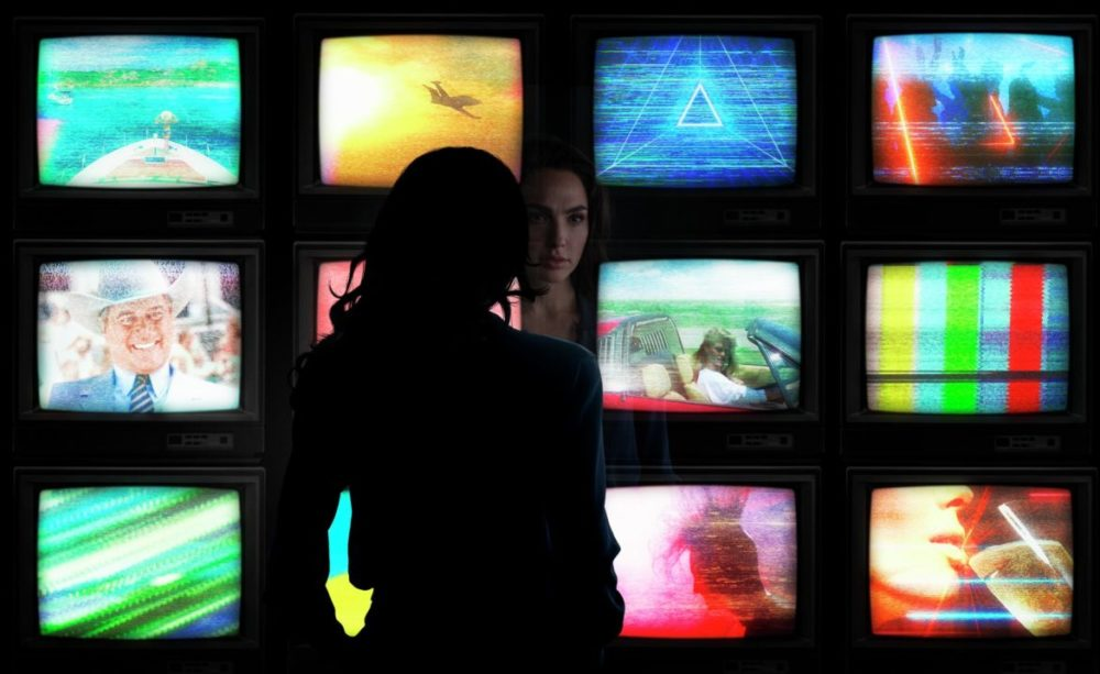 PhotoCredit Clay Enos/ ™ & © DC Comics CopyrightNotice © 2018 WARNER BROS. ENTERTAINMENT INC. Wonder Woman 1984 - Wonder Woman looks at tv screens.